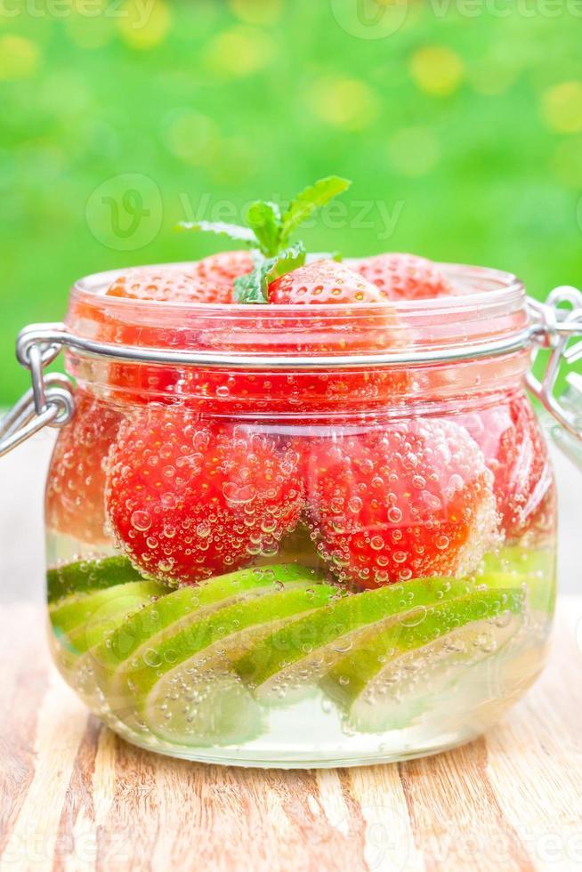 bebida caseira de frutas com limão e hortelã na mesa de morango foto