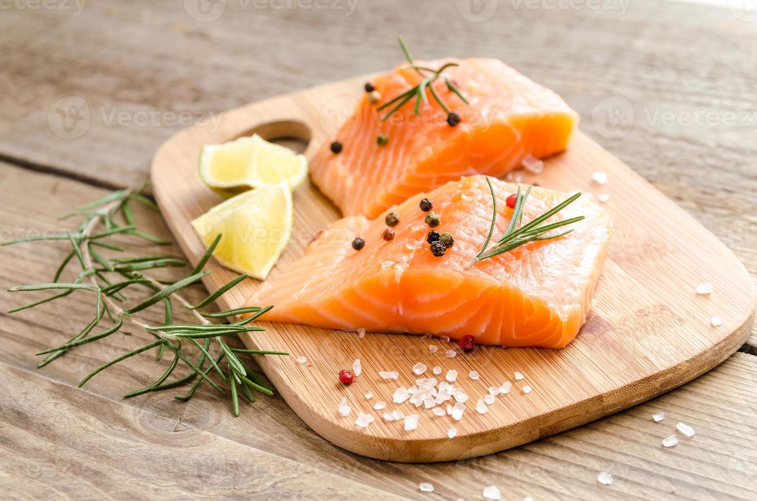 bifes de salmão cru na placa de madeira foto