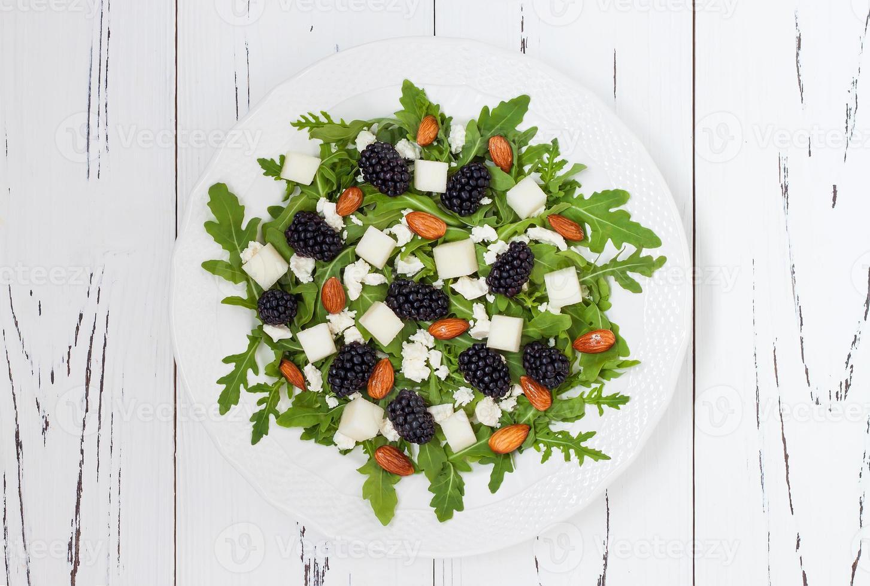 salada verde com rúcula, melão, amoras, amêndoas e queijo feta foto