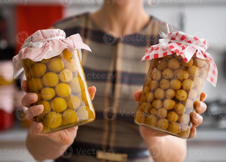 closeup de ameixas amarelas e groselhas em potes de vidro foto