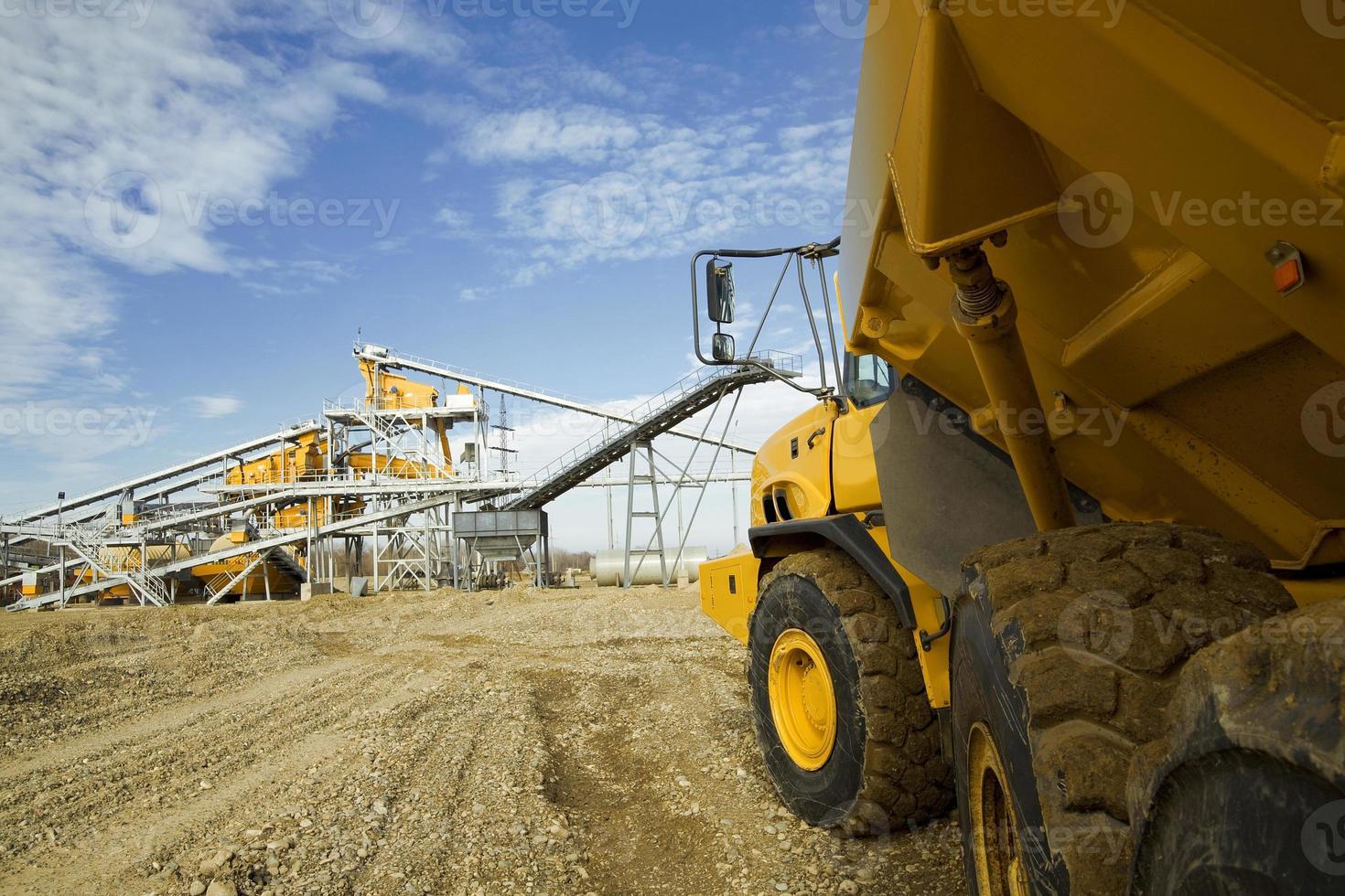 grande caminhão amarelo dirigindo para um canteiro de obras foto