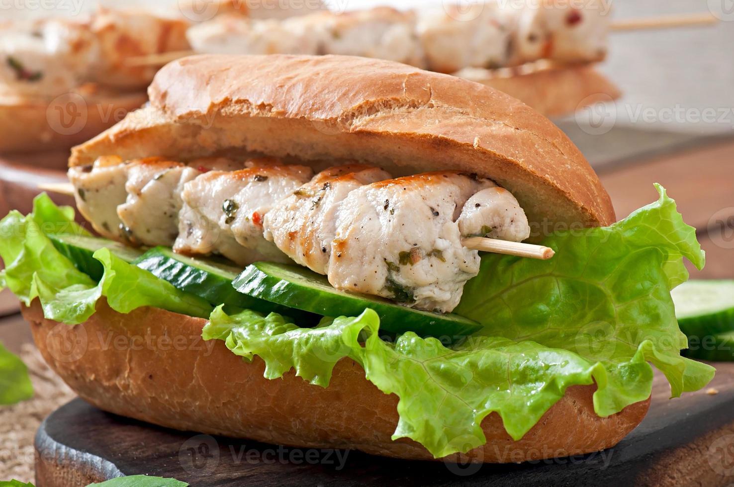 sanduíche grande com kebab de frango e alface foto