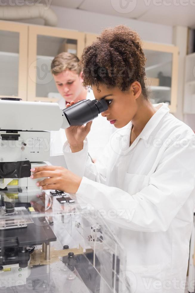 estudante de ciência bonita usando microscópio foto