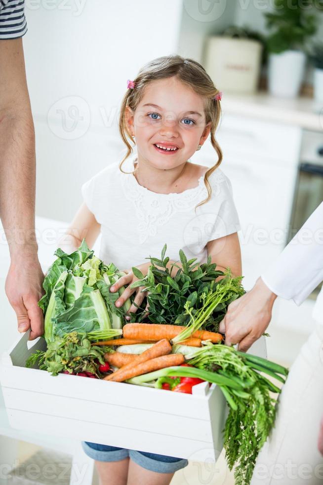 pai e filha com caixa de legumes na cozinha foto