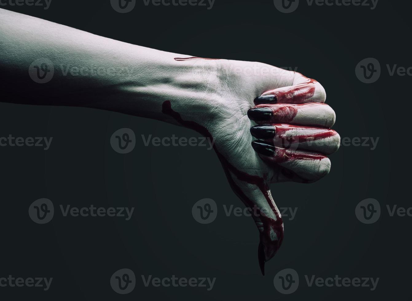 mão de vampiro mostra o polegar para baixo gesto foto