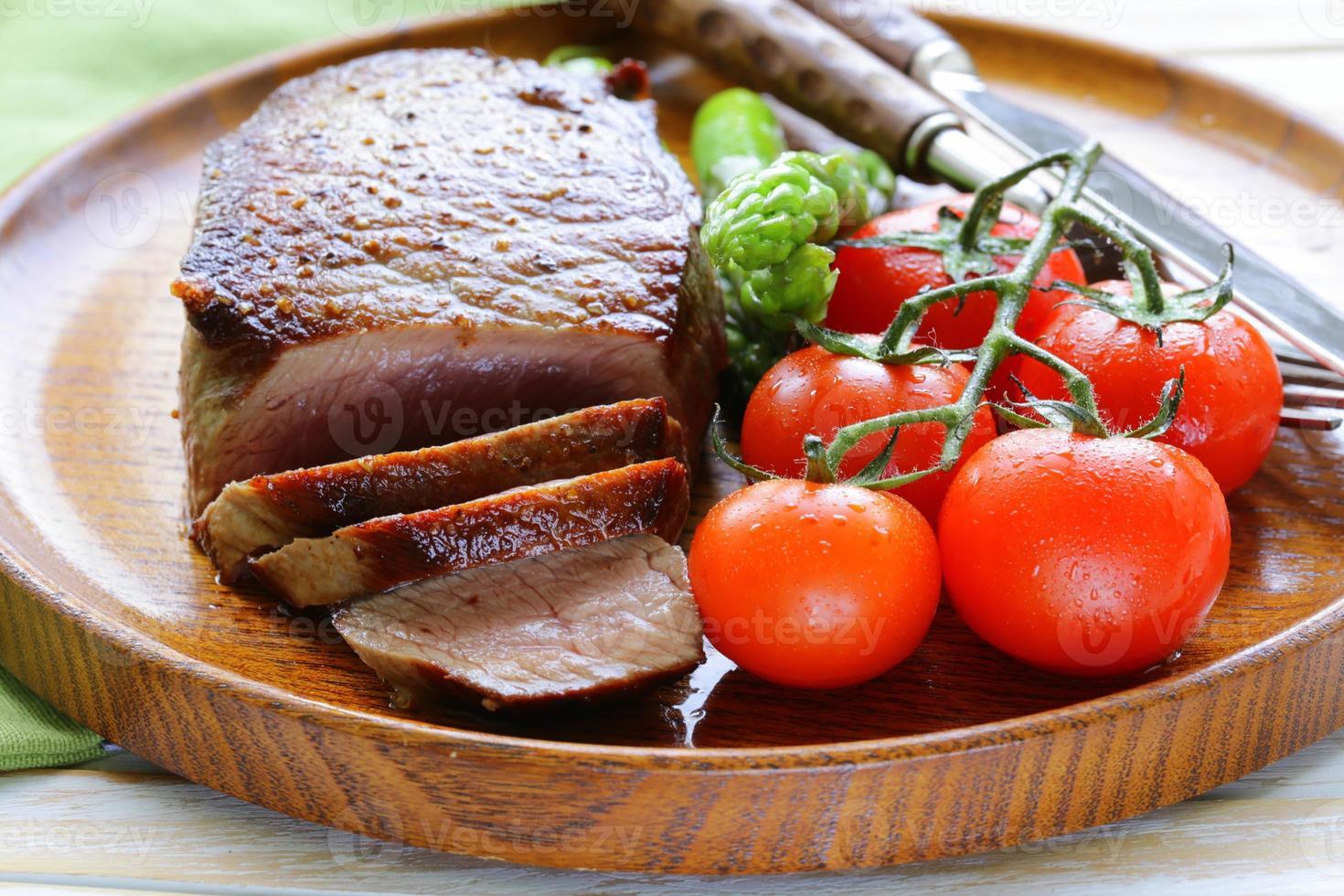 bife de carne grelhada com guarnição de legumes (aspargos e tomates) foto