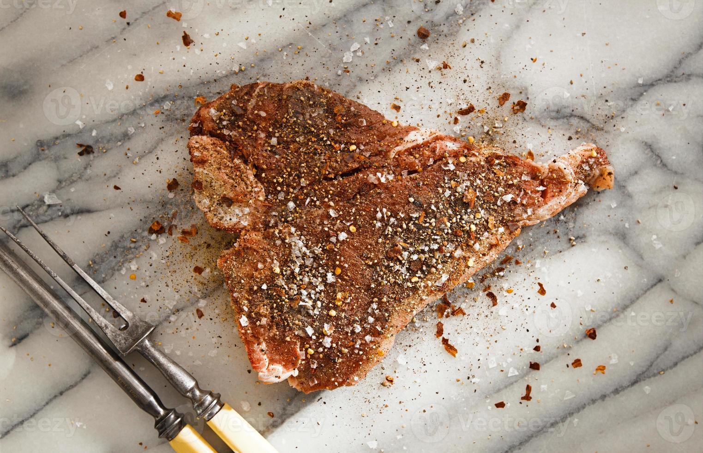 t-bone de carne com garfo de carne vintage no pano de fundo de mármore foto