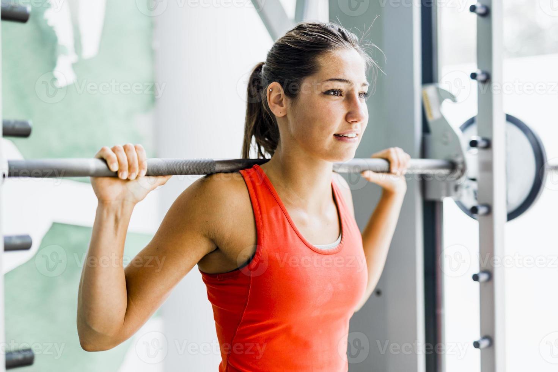 jovem e bela mulher levantando pesos em uma academia foto