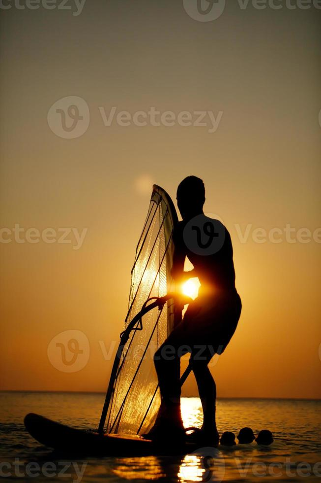 homem surfando ao pôr do sol foto