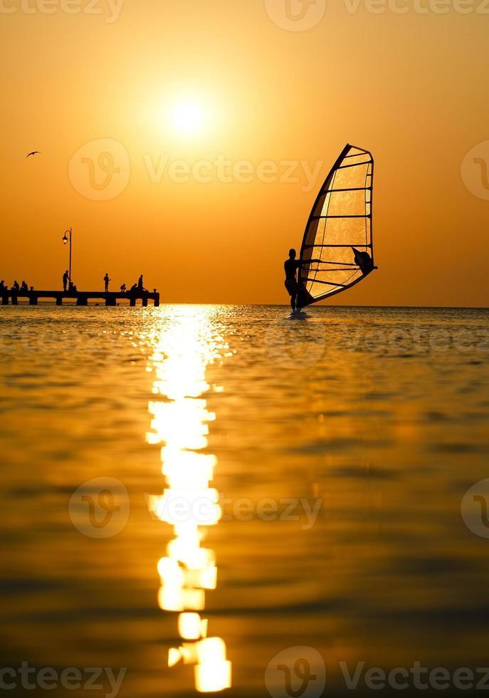 silhueta de surfista ao pôr do sol passando foto