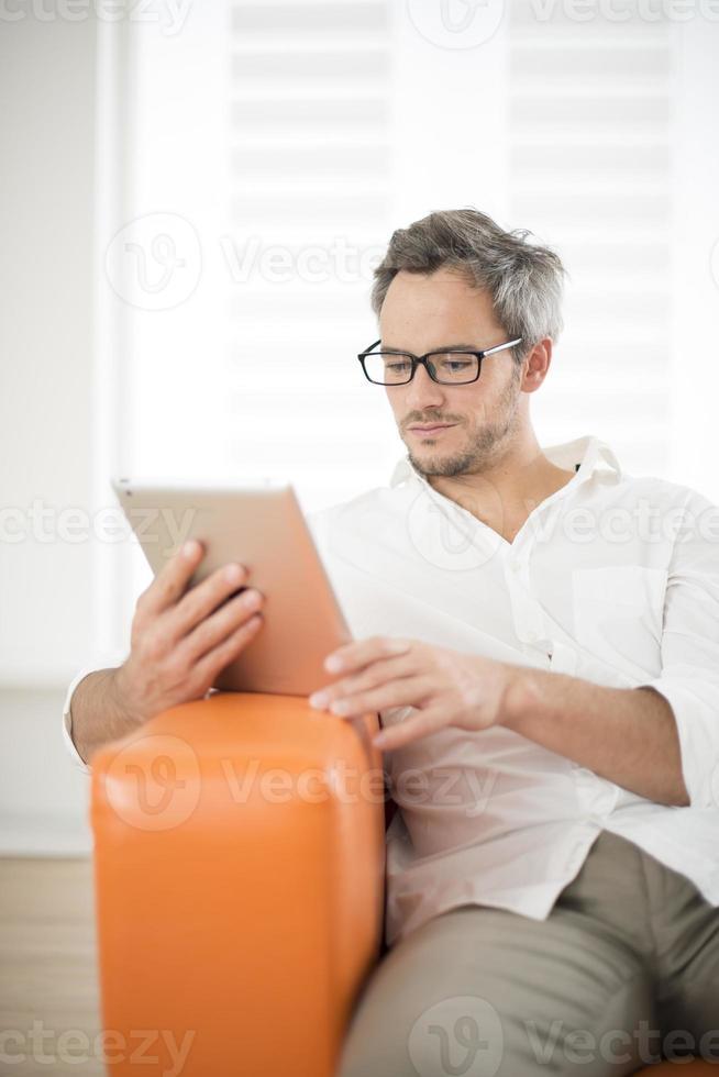 homem bonito surfando no tablet foto