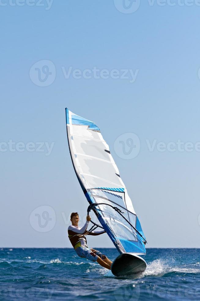 windsurfista surfando em direção à câmera com céu claro foto