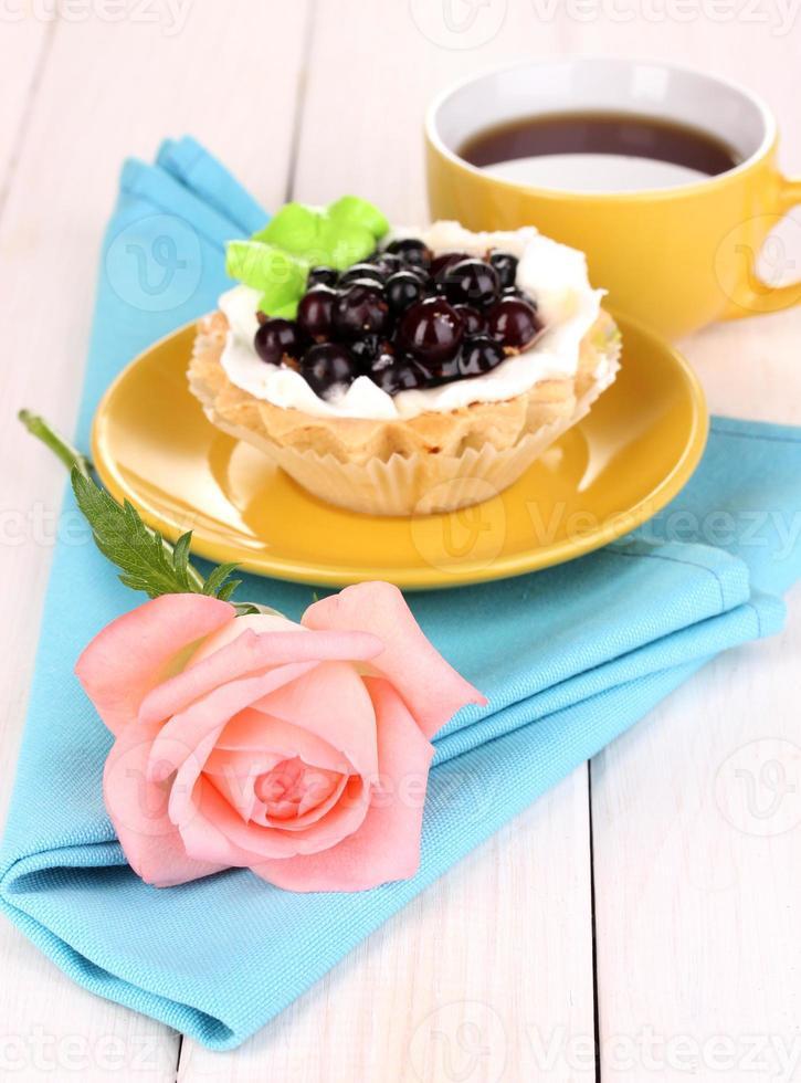 bolo doce com uma xícara de chá em fundo de madeira foto