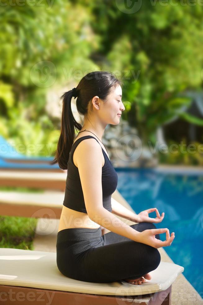 menina asiática praticando ioga foto