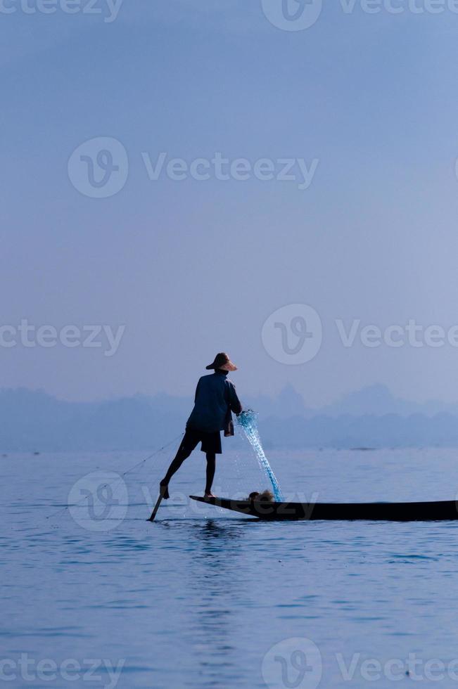 pescador no lago inle trabalhando em um pé foto