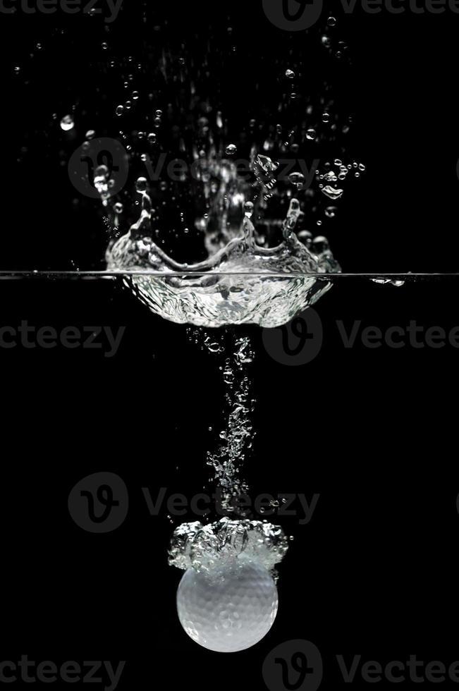 bola de golfe espirrando na água foto