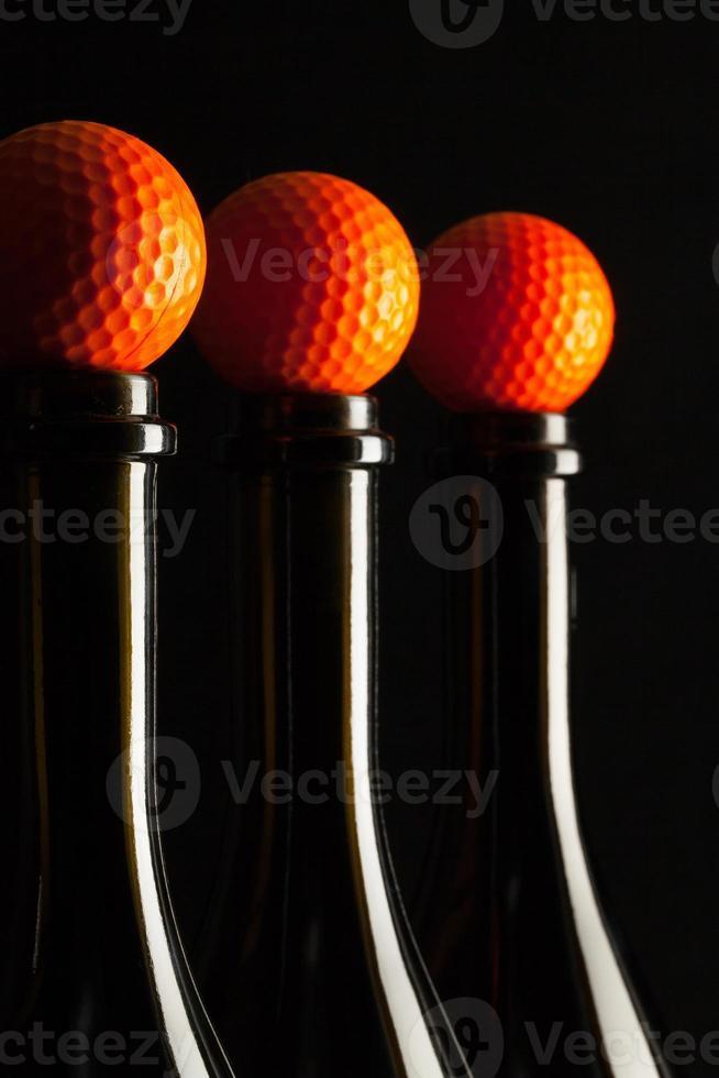 silhuetas de elegantes garrafas de vinho com bolas de golfe foto