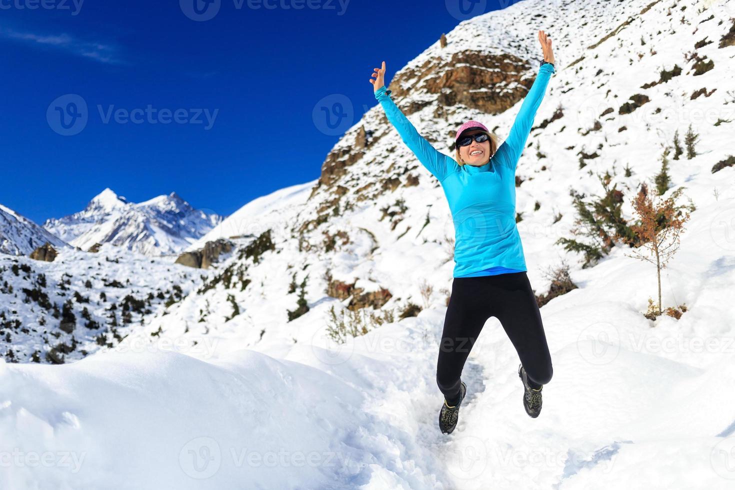 mulher pulando e correndo nas montanhas de inverno foto