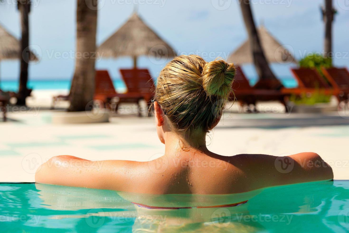 garota na piscina no paraíso resort foto