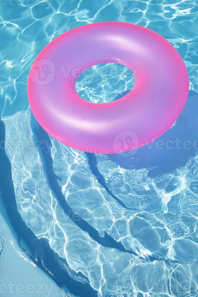 anel rosa flutuando em uma piscina azul foto