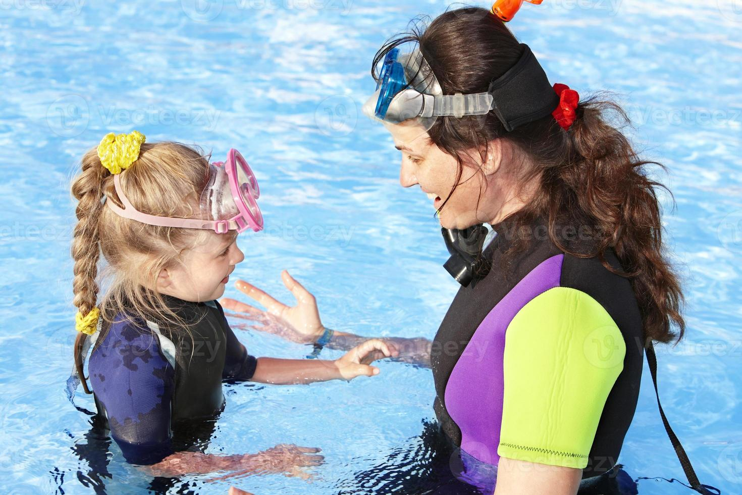 criança com a mãe na piscina. foto