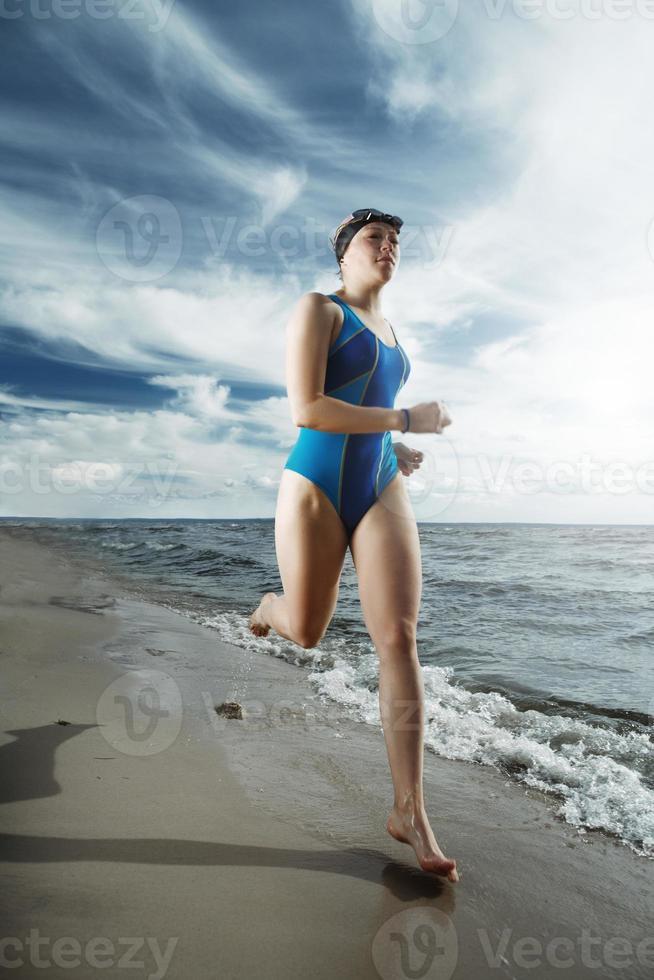 atleta jovem correndo na praia foto
