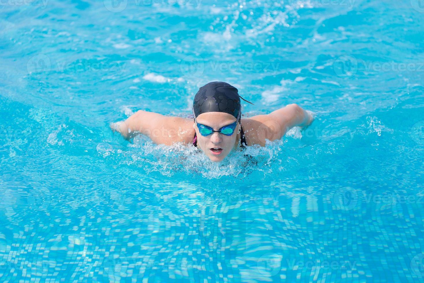 jovem nadando estilo de traçado de borboleta foto