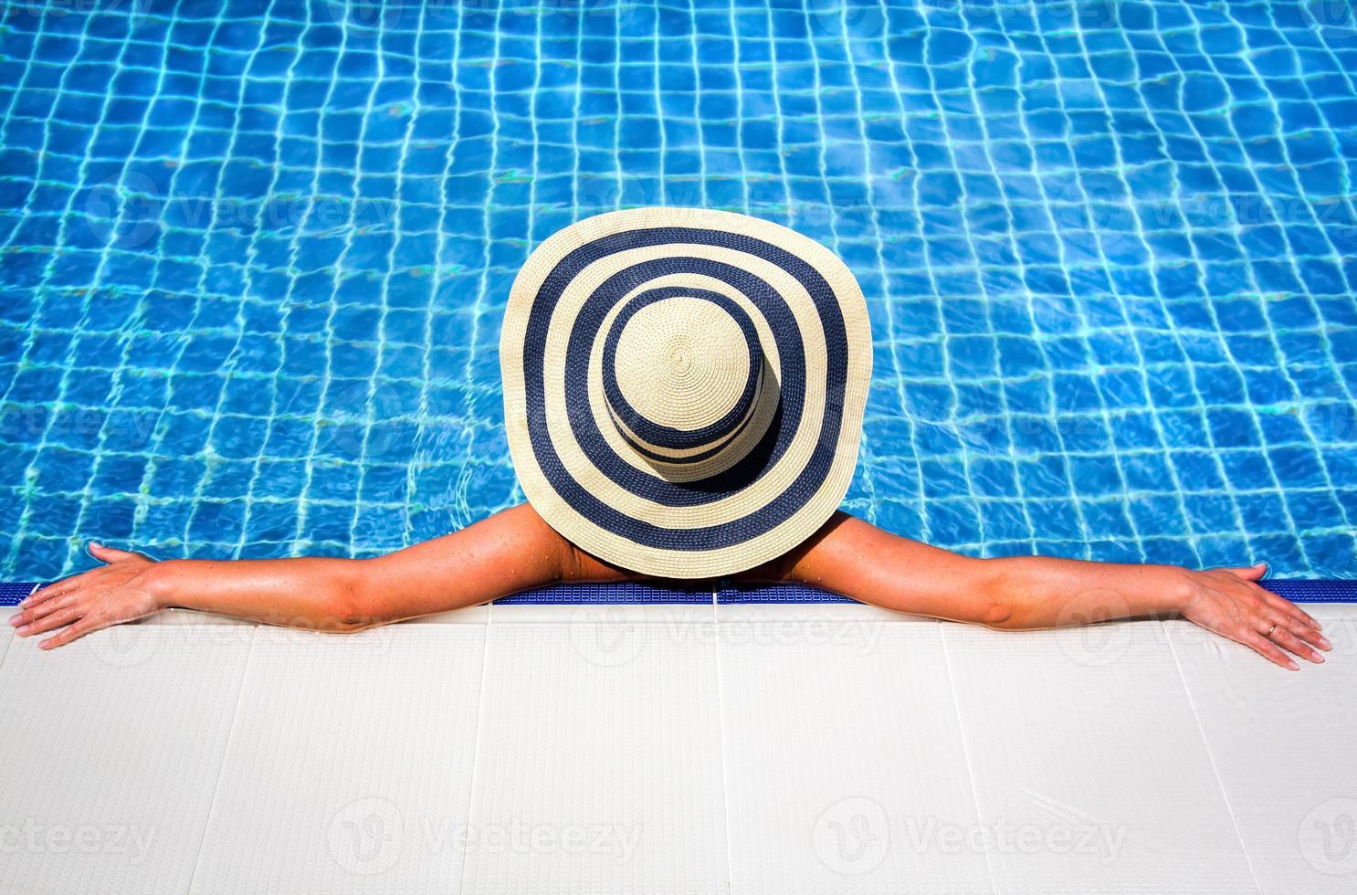 mulher de chapéu de palha relaxante piscina foto