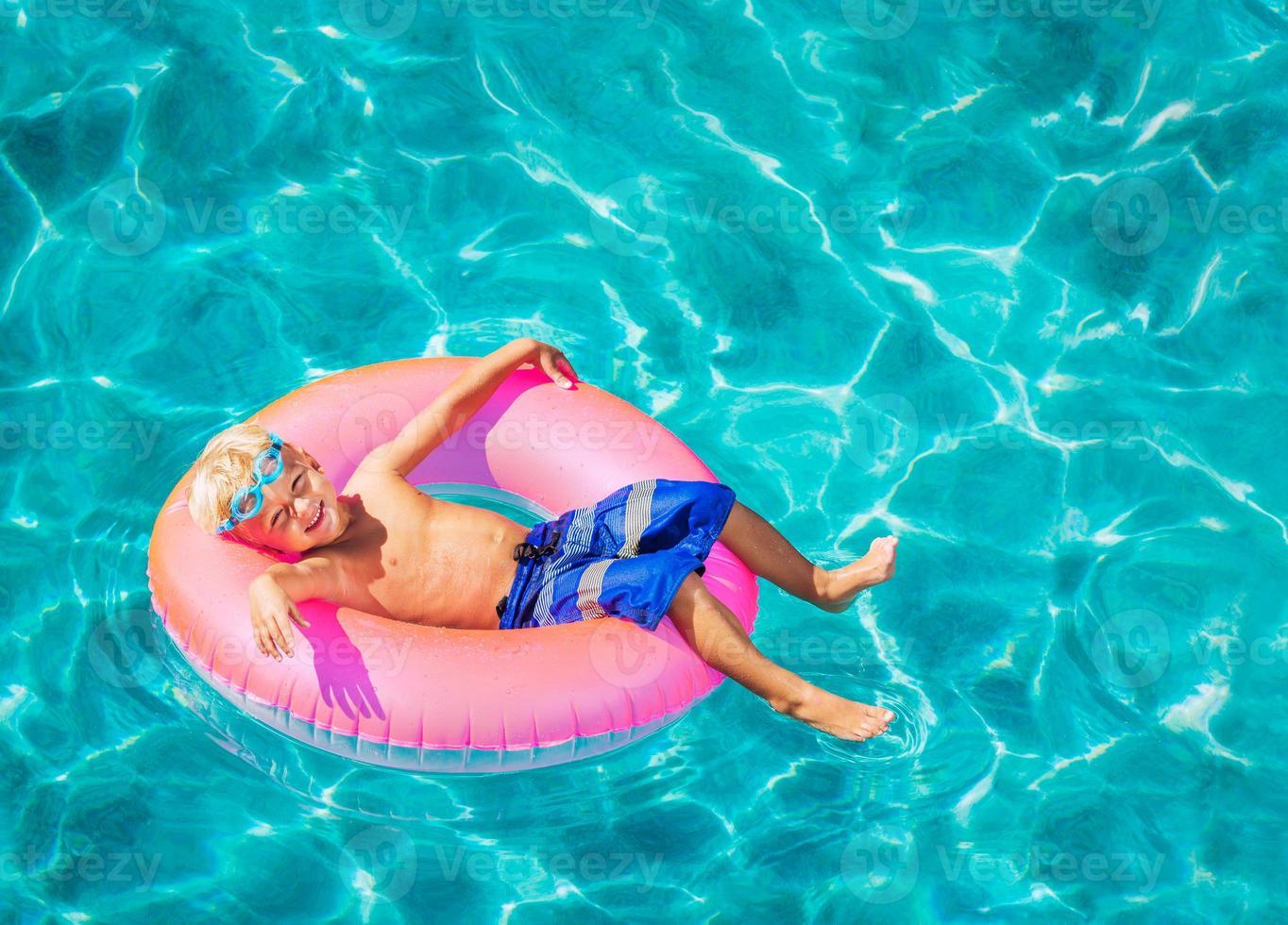 garoto se divertindo na piscina foto