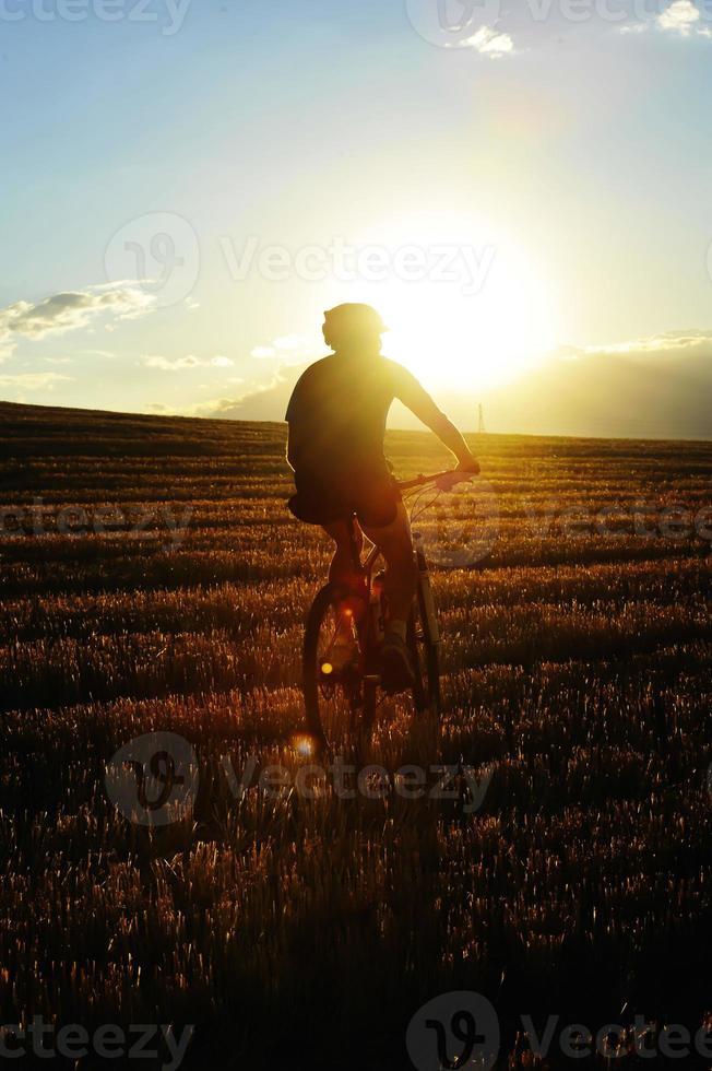 ciclista de montanha andando pelo campo de palha ao pôr do sol foto