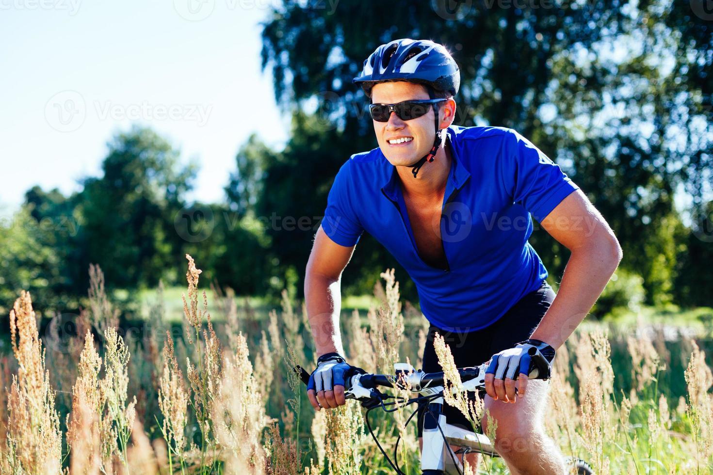jovem feliz andando de bicicleta lá fora. estilo de vida saudável. foto
