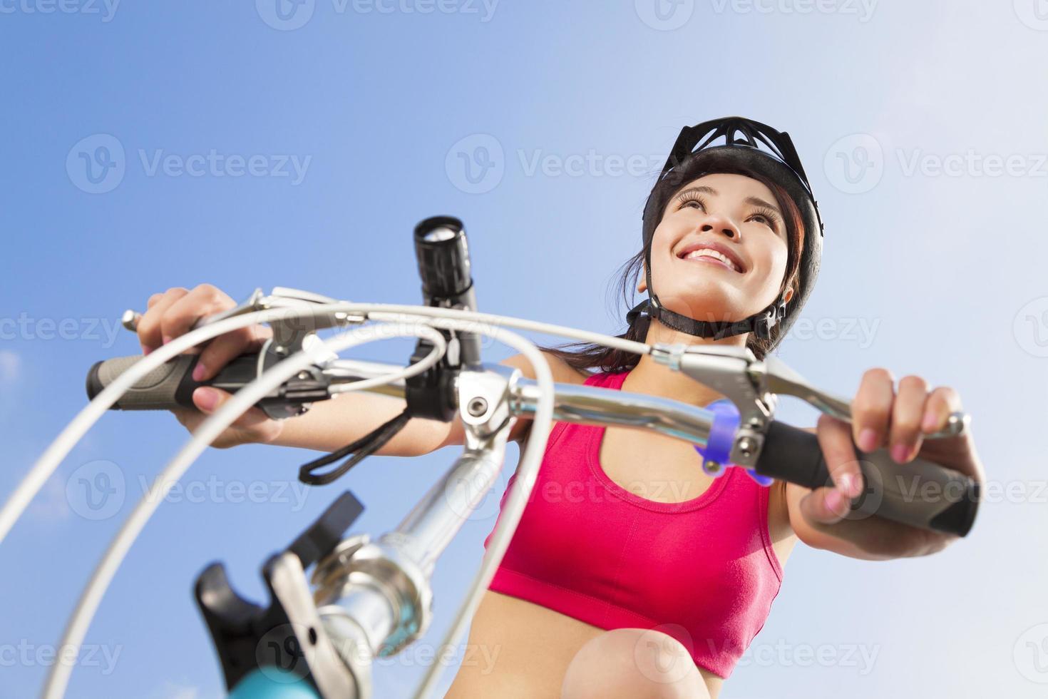 motociclista feminina, começando a andar com céu azul foto