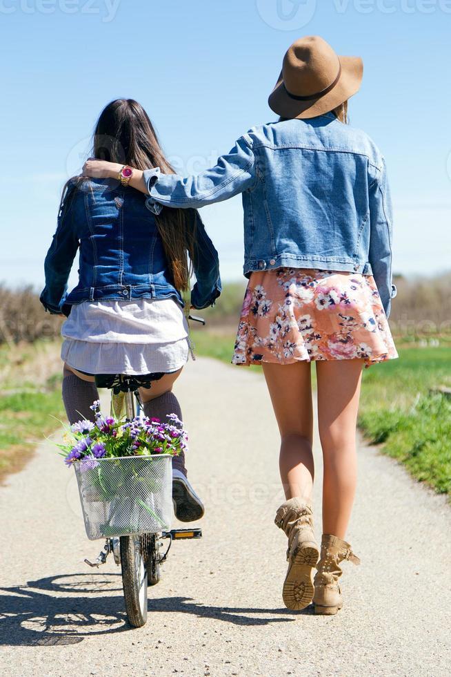 duas mulheres jovens com uma bicicleta vintage no campo. foto
