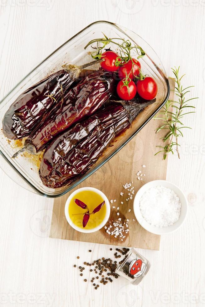 berinjela assada e tomate cereja na bandeja do forno em branco. estação foto