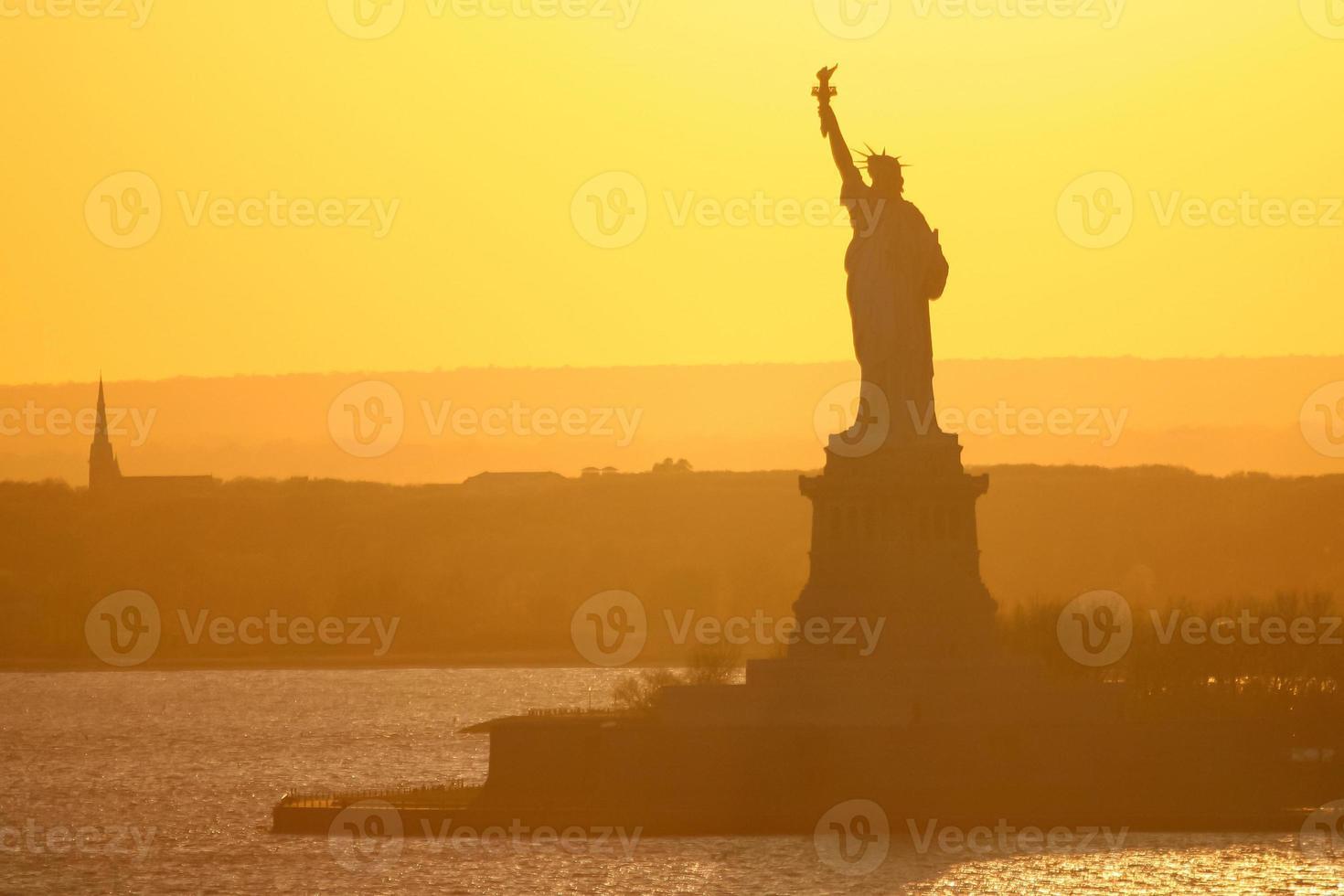 estátua da liberdade em new york city ao pôr do sol foto