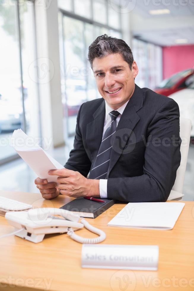 vendedor sorridente segurando um documento foto
