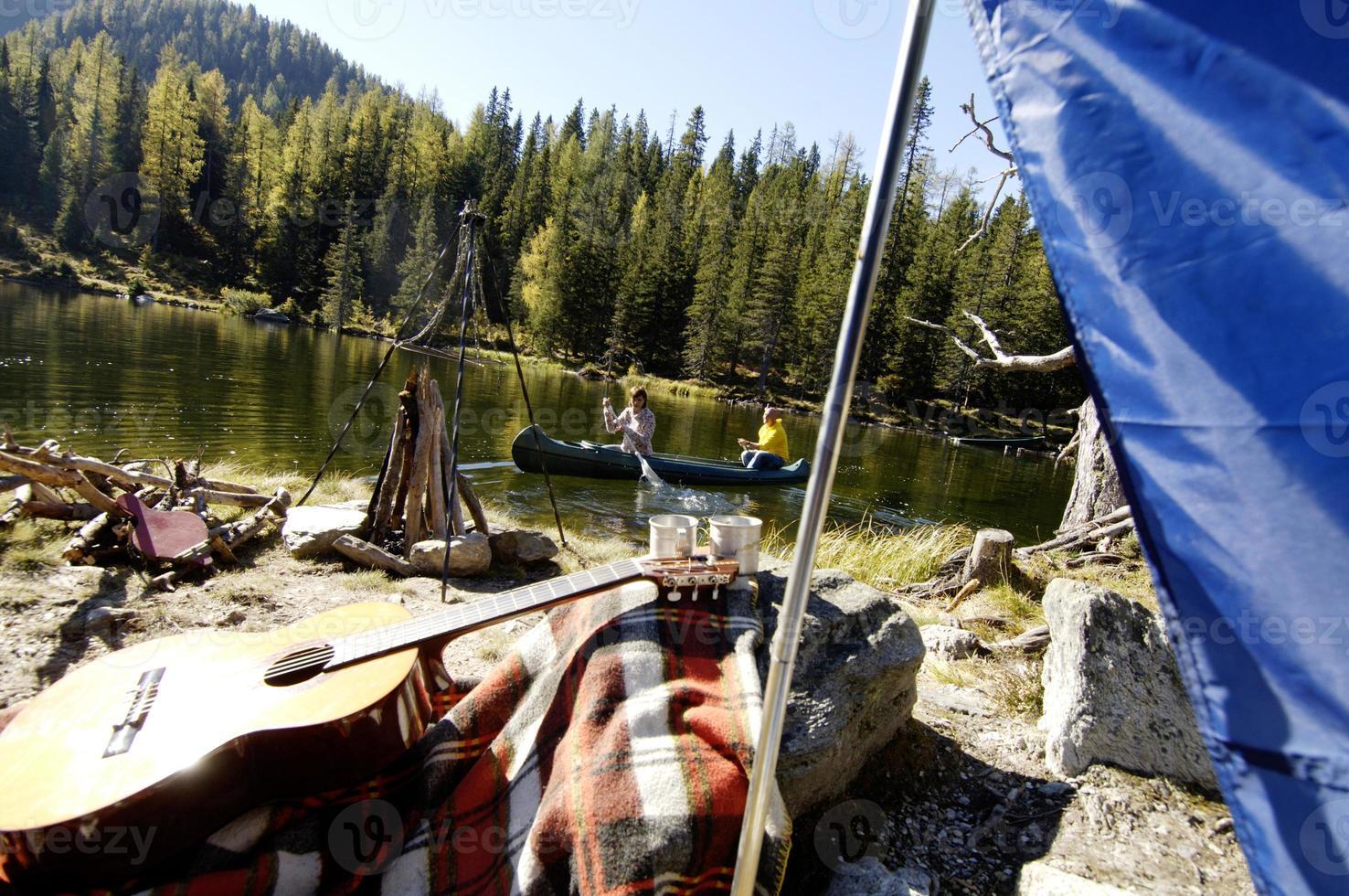 homem e mulher saindo do acampamento em canoa foto
