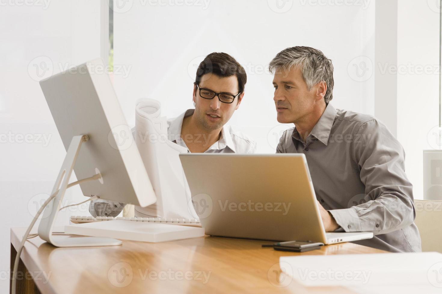 dois empresários discutindo uma planta em um escritório foto
