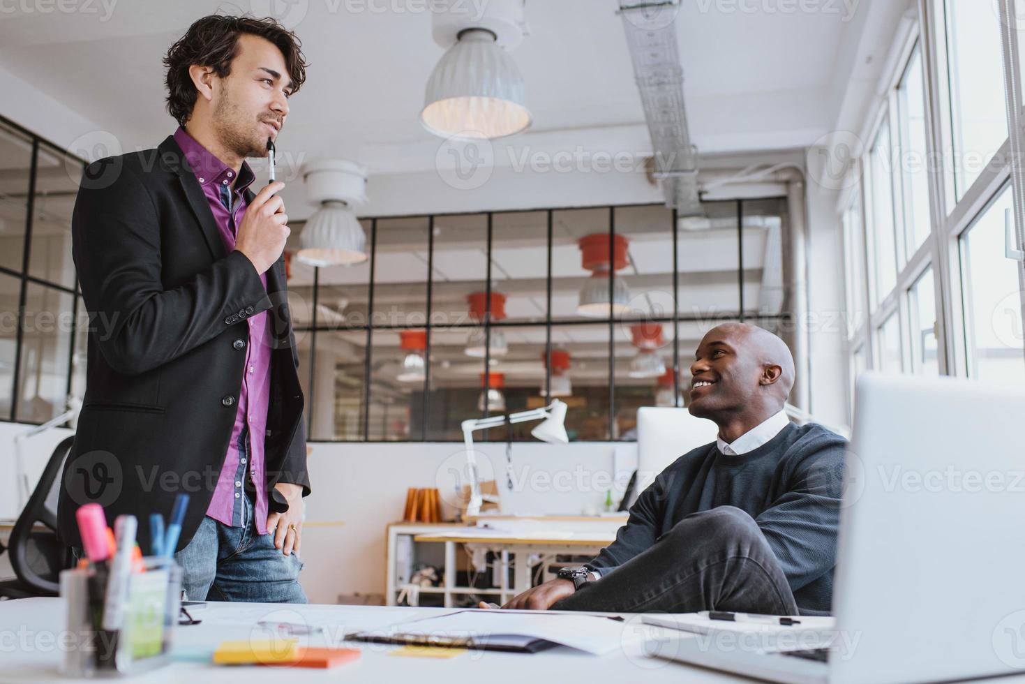 dois trabalhadores de escritório jovem discutindo o trabalho no escritório foto