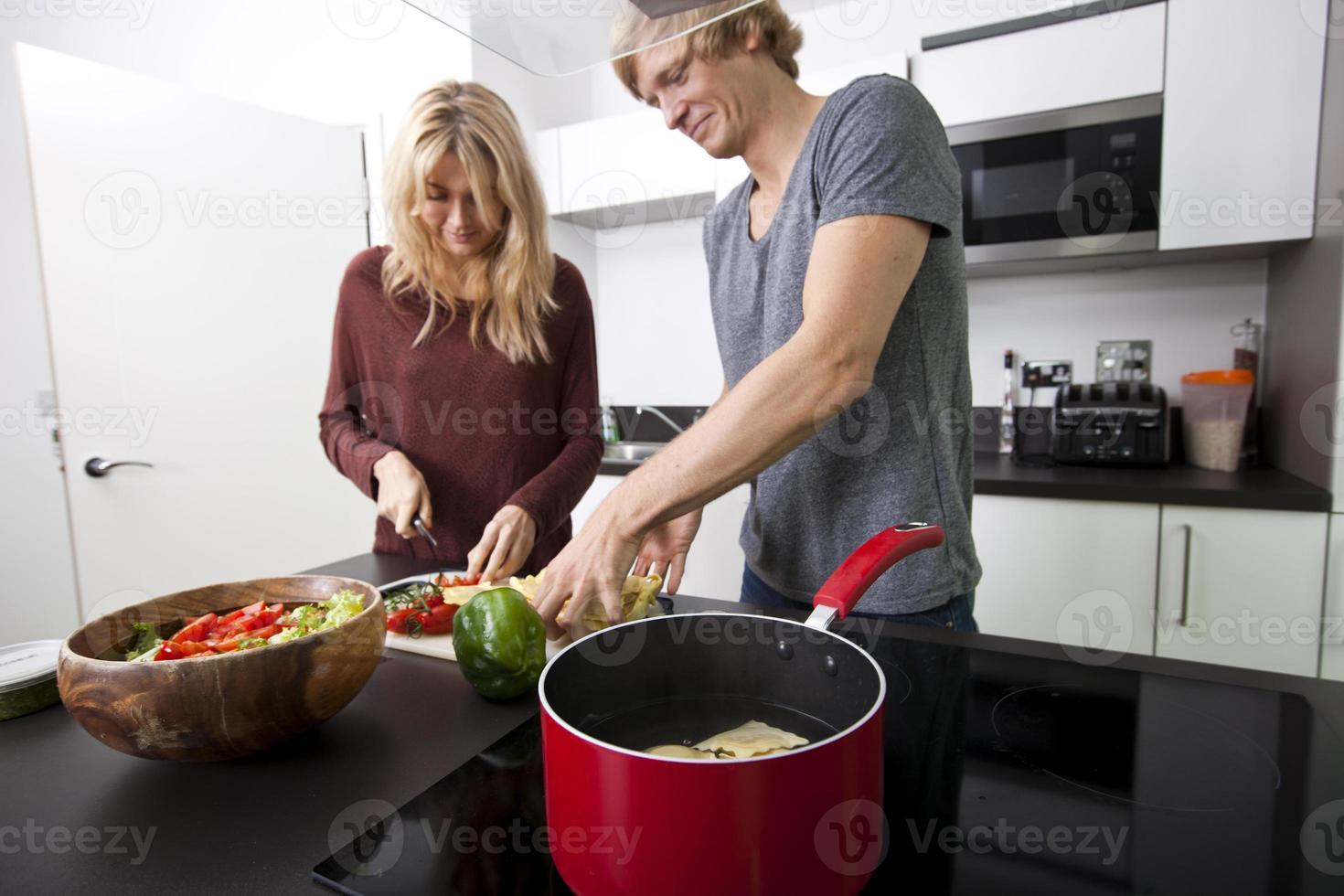 casal caucasiano cozinhar macarrão juntos na cozinha foto