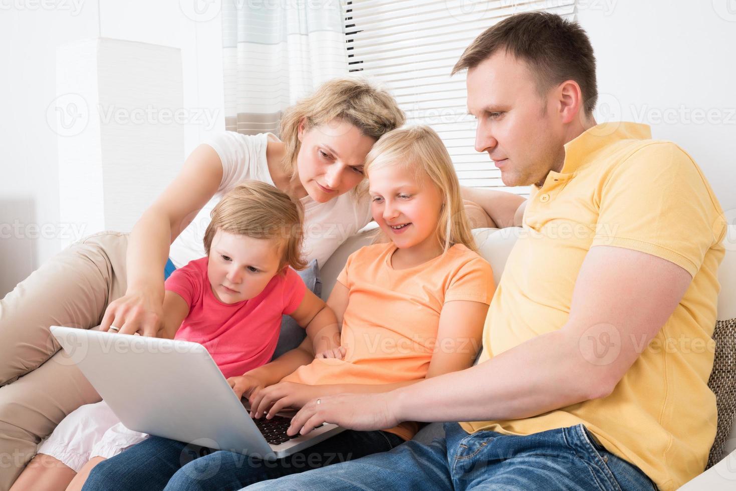 família usando laptop no sofá foto