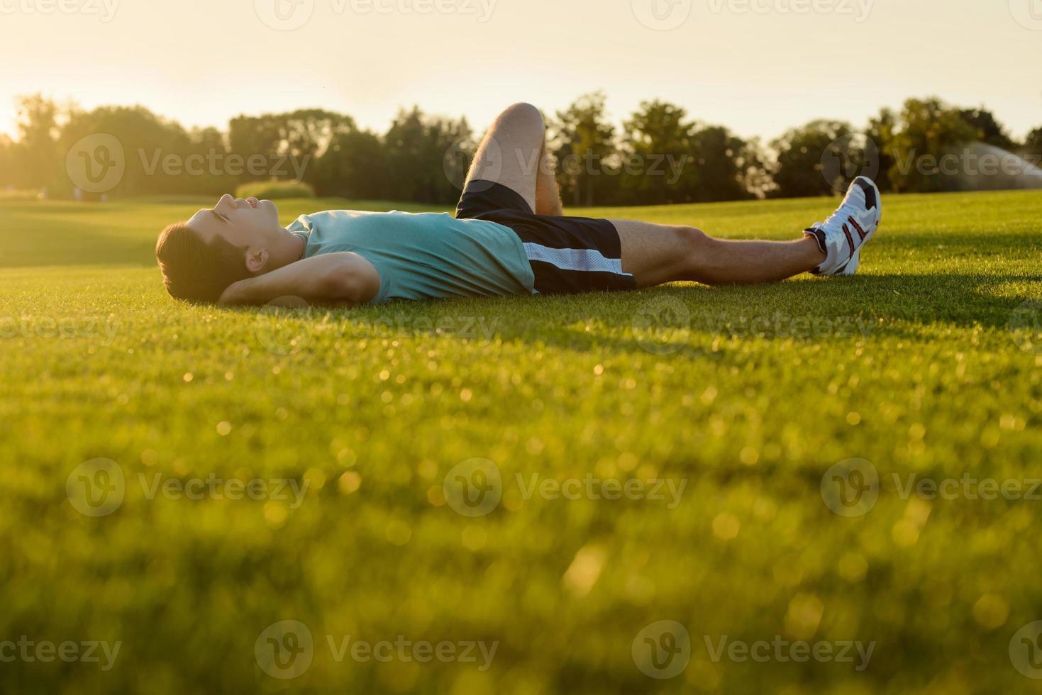 cara deitado no parque ao pôr do sol. foto