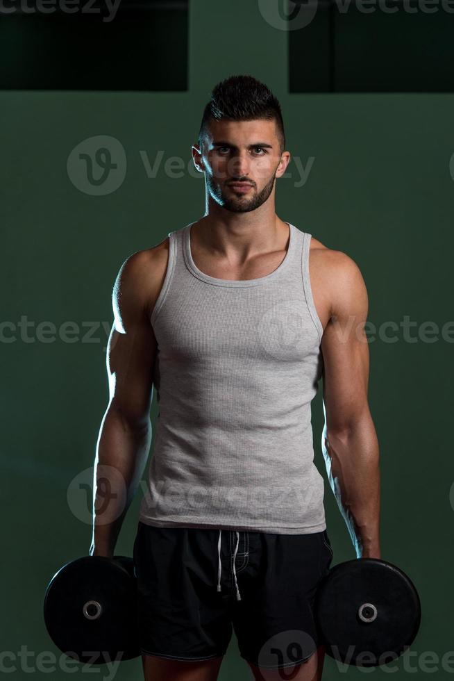 homens no ginásio exercitar com halteres foto
