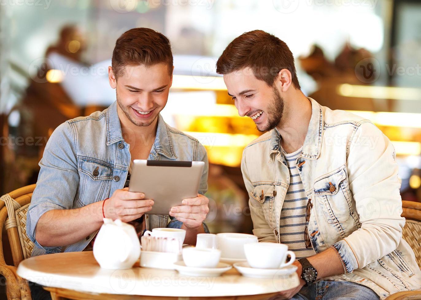 dois jovens / estudantes usando computador tablet no café foto