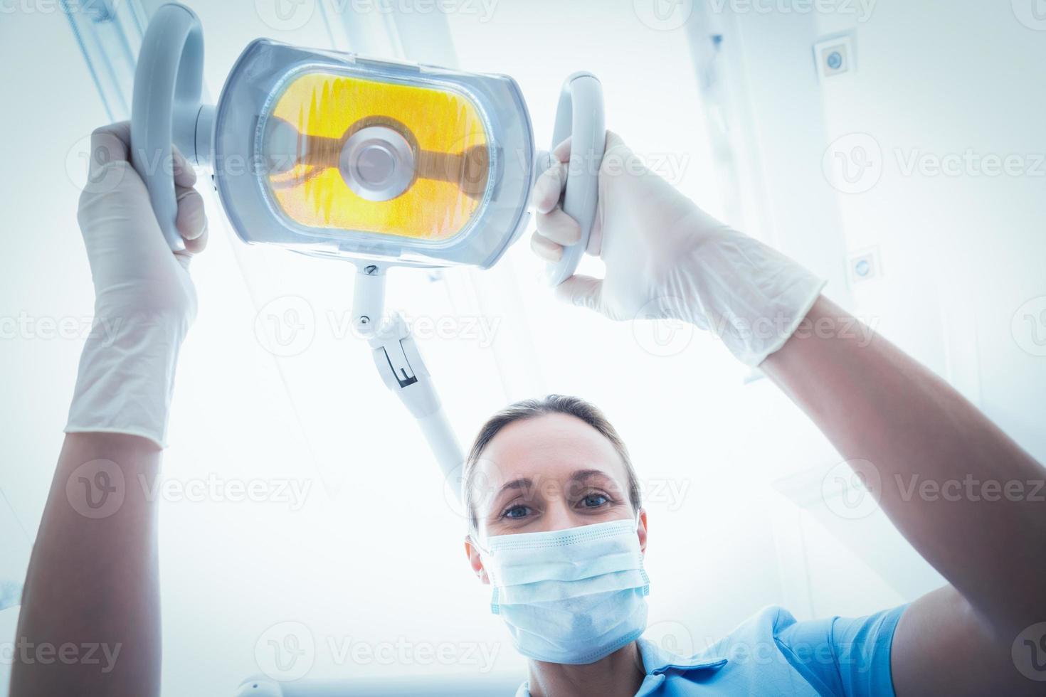 dentista feminino, ajustando a luz foto