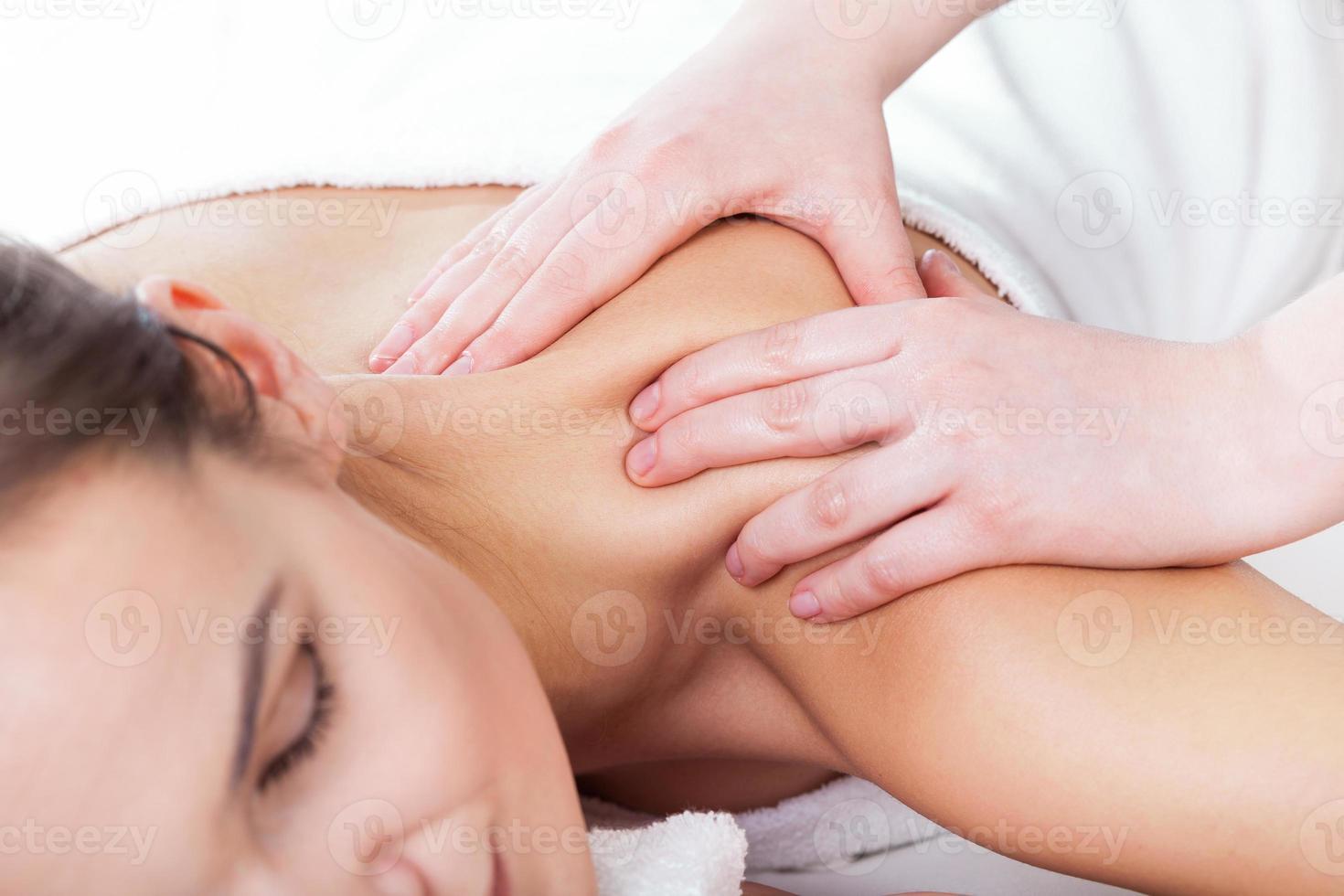 mãos massageando pescoço feminino foto