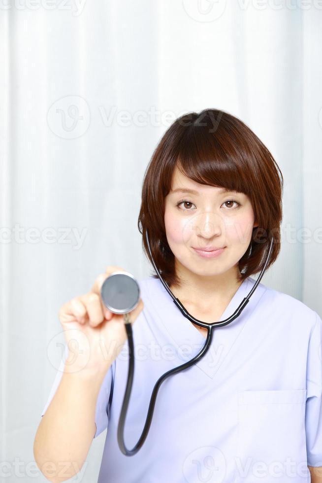 médico feminino japonês com estetoscópio foto