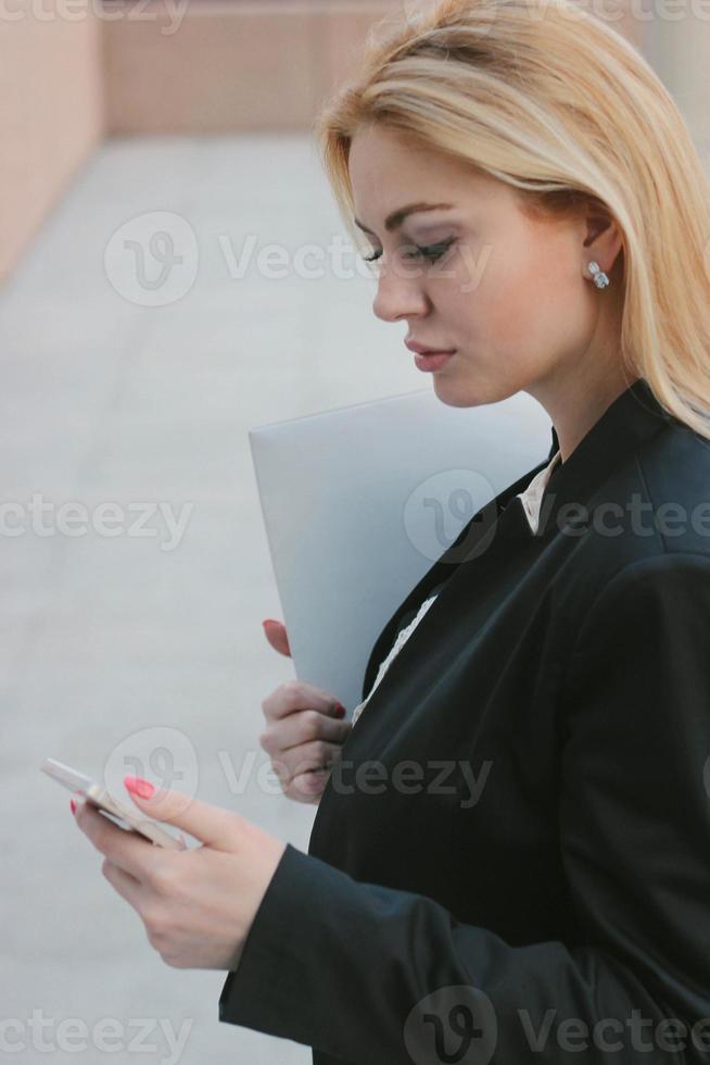 modelo feminino com móvel do lado de fora foto