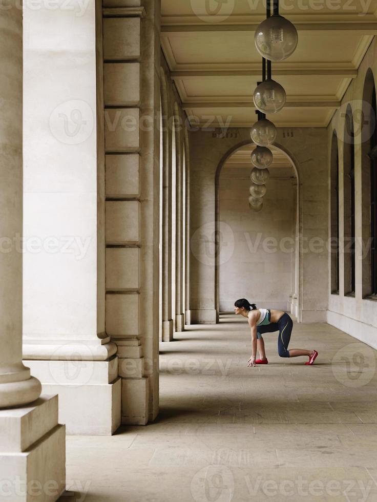 corredor feminino agachado no pórtico foto