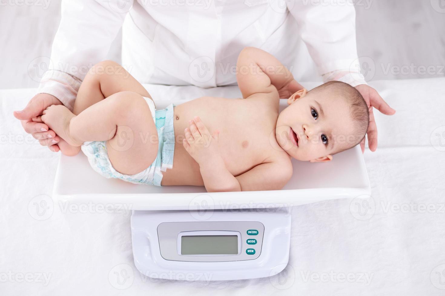 pediatra feminino pesando bebê no escritório foto